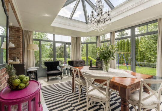 Creative conservatory with glass roof, chandelier, dining table and armchairs