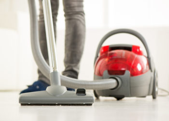 person vacuuming the house with focus on legs and vacuum cleaner
