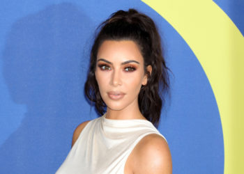 Kim Kardashian at an Award Show standing in front of a blue background