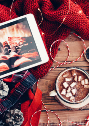 Tablet with Christmas movie and warm knit sweater and cup of hot cocoa with marshmallows. Christmas lollipop, led lights string and other holiday decor