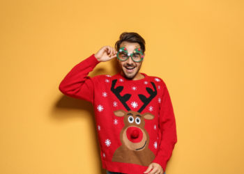 man in front of yellow background wearing a reindeer christmas jumper and Christmas glasses