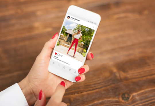 Female hand holding smartphone with instagram app opened showing the picture of a fashion blogger.