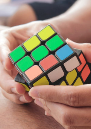 two hands turning a colourful rubic's cube