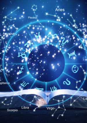 open book and star signs on dark background symbolizing horoscopes