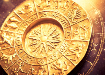 a gold zodiac wheel over a horoscope