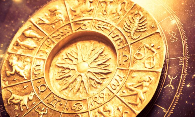 a gold zodiac wheel over a horoscope