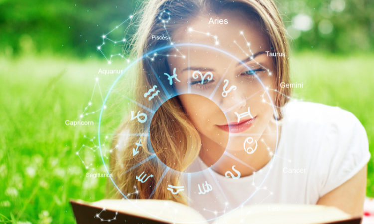 young woman reading a book with horoscope star signs above