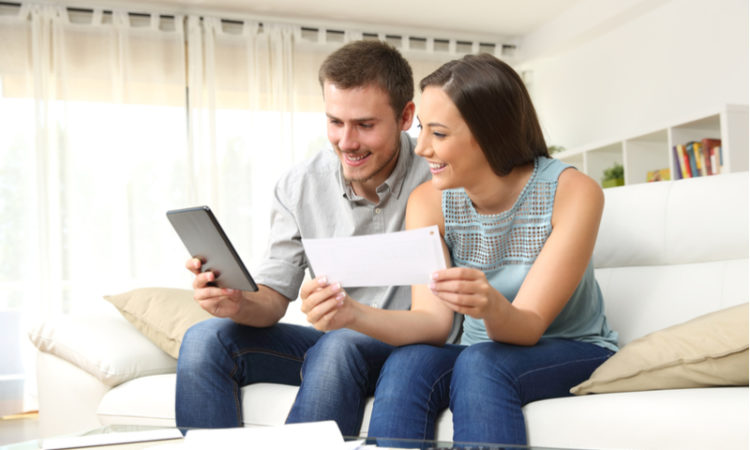 Young couple doing an online loan application from home through a tablet