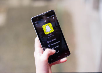 hand holding smartphone with Snapchat App