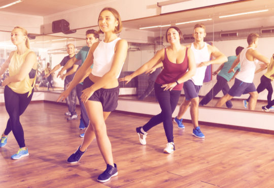 group of young people dancing a choreography in a dance studio