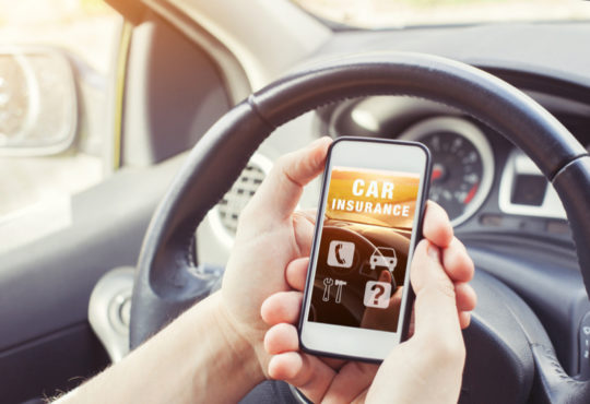 hands holding a smartphone sitting in a car with the words car insurance