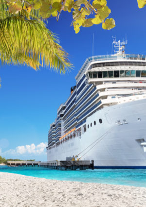 luxury cruise ship close to a beautiful beach with palm trees