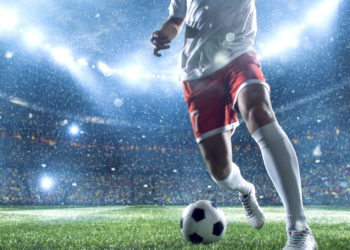 Soccer player with ball in soccer stadium