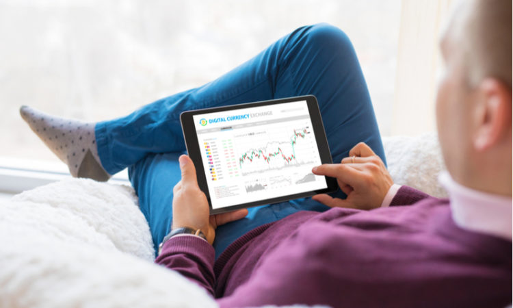 Man sitting on the sofa and using an online trading app on his tablet