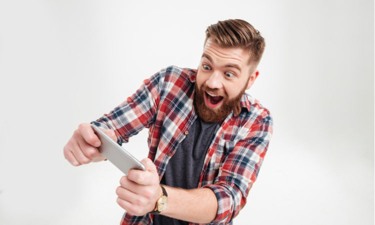 Excited bearded man in plaid shirt playing a mobile football game on smartphone
