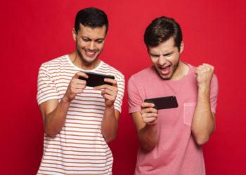 Two young men standing in front of red background, playing games on mobile phone