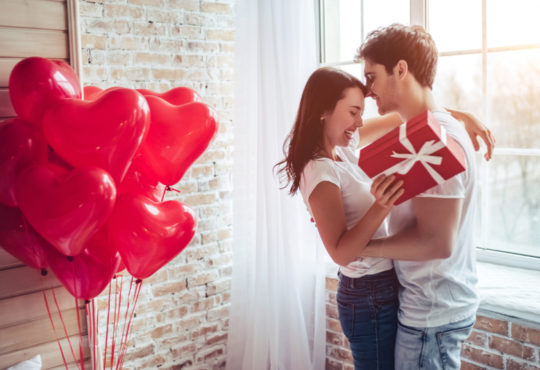 Beautiful young couple at home hugging and kissing at Valentines Day with red heart balloons and gift
