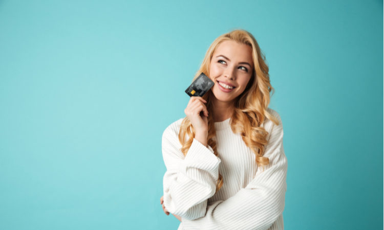 Portrait of a young blonde woman in sweater showing credit card