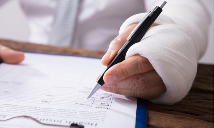 Businessperson With Broken Arm Filling Health Insurance Claim Form