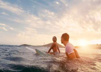 Fit couple surfing at sunset in Australia, Oceania