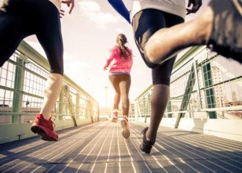 Three runners sprinting outdoors running a marathon over a bridge
