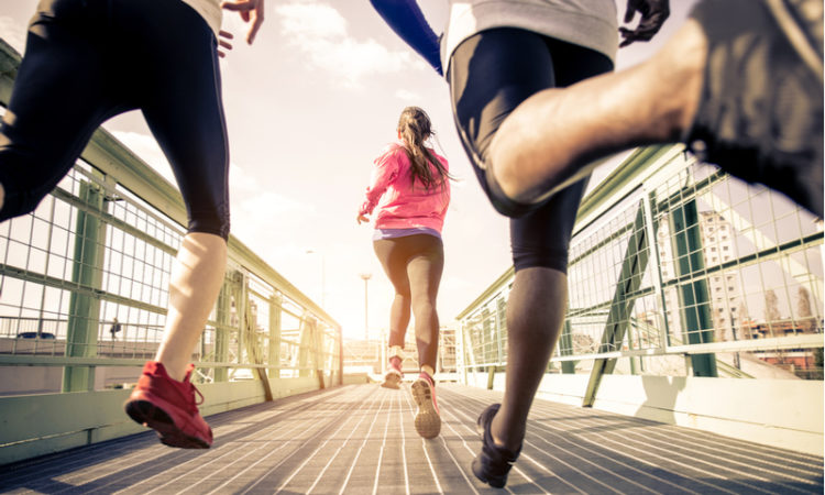 Three runners sprinting outdoors running a marathon over a bridge
