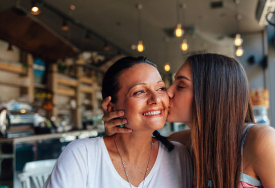 young woman kissing her mother on the cheek on Mother's Day