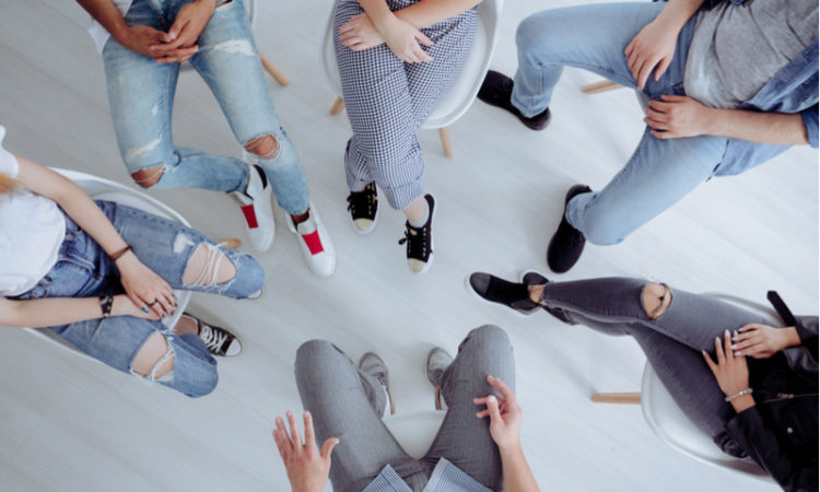 High angle of rehab specialist and addicts sitting in a circle during a meeting