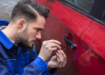 Auto locksmith opening the lock of a car