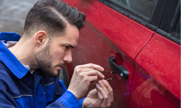 Auto locksmith opening the lock of a car